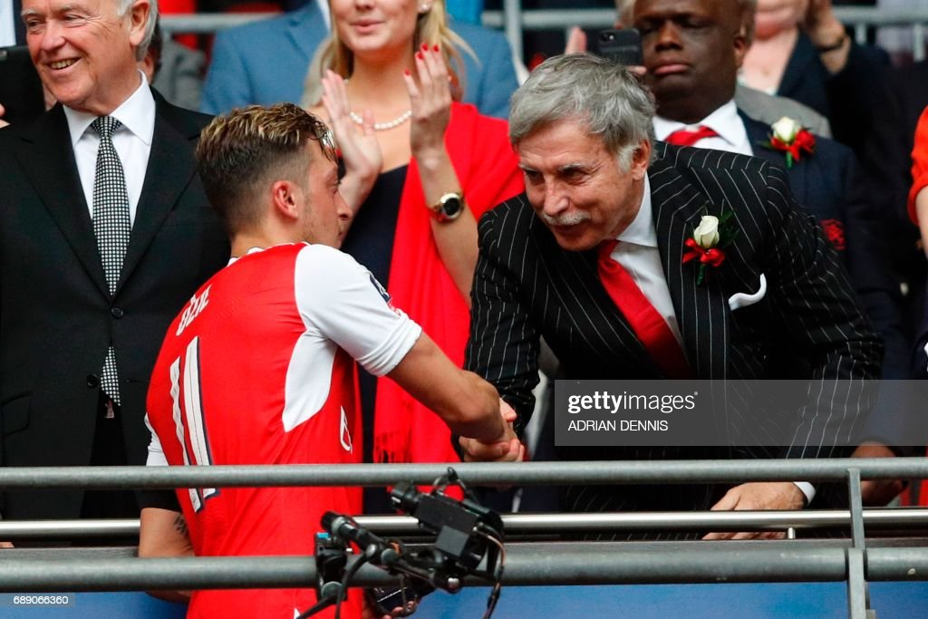 Arsenal's US owner Stan Kroenke shakes hands with Arsenal's German midfielder Mesut Ozil (2nd L) as Arsenal players celebrate their victory over Chelsea in the English FA Cup final football match between Arsenal and Chelsea at Wembley stadium in London on May 27, 2017. Aaron Ramsey scored a 79th-minute header to earn Arsenal a stunning 2-1 win over Double-chasing Chelsea on Saturday and deliver embattled manager Arsene Wenger a record seventh FA Cup. / AFP PHOTO / Adrian DENNIS / NOT