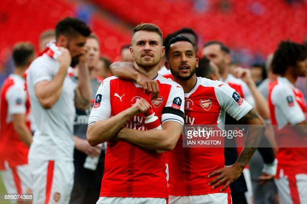 Arsenal's Welsh midfielder Aaron Ramsey and Arsenal's English midfielder Theo Walcott celebrate on the pitch after their win over Chelsea in the...