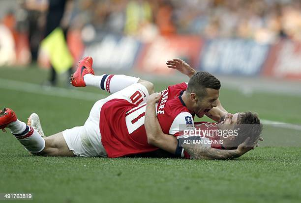 Arsenal's Welsh midfielder Aaron Ramsey celebrates scoring his team's third and winning goal with Arsenal's English midfielder Jack Wilshere during...