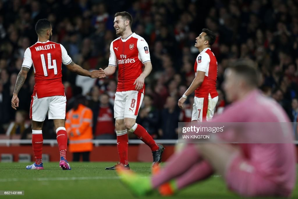 Arsenal's Welsh midfielder Aaron Ramsey (2nd L) celebrates with Arsenal's English midfielder Theo Walcott (L) after scoring their fifth goal during the English FA cup quarter final football match between Arsenal and Lincoln City at The Emirates Stadium in London on March 11, 2017. / AFP PHOTO / Ian KINGTON / RESTRICTED TO EDITORIAL USE. No use with unauthorized audio, video, data, fixture lists, club/league logos or 'live' services. Online in-match use limited to 75 images, no video emulation. No use in betting, games or single club/league/player publications. /