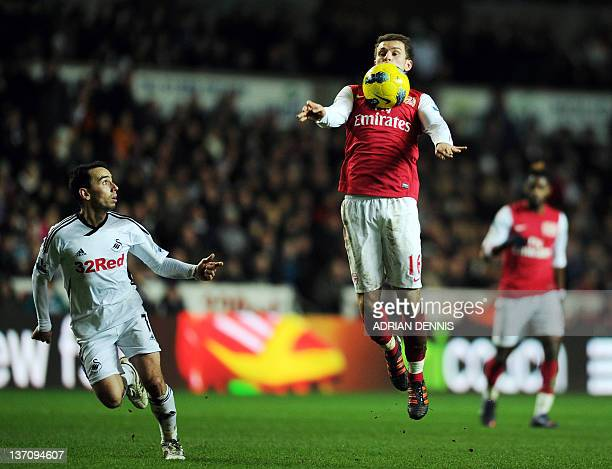 Arsenal's Welsh midfielder Aaron Ramsey controls the ball next to Swansea City's Leon Britton during their English Premiership football match at the...