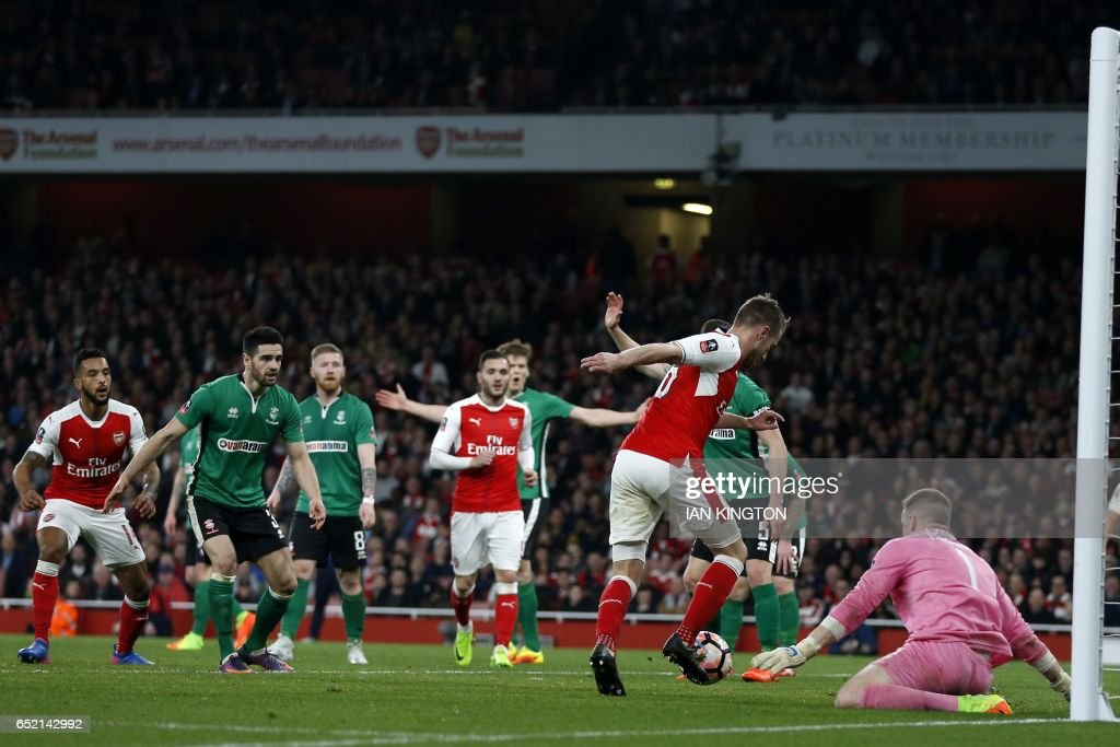 Arsenal's Welsh midfielder Aaron Ramsey (2nd R) goes around Lincoln City's English goalkeeper Paul Farman (R) on his way to scoring their fifth goal during the English FA cup quarter final football match between Arsenal and Lincoln City at The Emirates Stadium in London on March 11, 2017. / AFP PHOTO / Ian KINGTON / RESTRICTED TO EDITORIAL USE. No use with unauthorized audio, video, data, fixture lists, club/league logos or 'live' services. Online in-match use limited to 75 images, no video emulation. No use in betting, games or single club/league/player publications. /