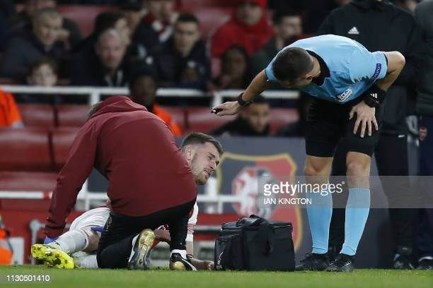 Arsenal's Welsh midfielder Aaron Ramsey receives medical treatment during the UEFA Europa League Round of 16 second leg football match between...