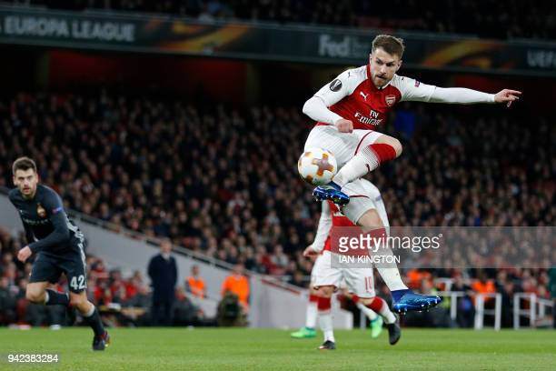 Arsenal's Welsh midfielder Aaron Ramsey scores their third goal with this flick during the UEFA Europa League first leg quarterfinal football match...
