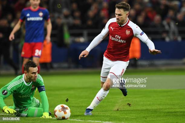 Arsenal's Welsh midfielder Aaron Ramsey vies for the ball against CSKA Moscow's Russian goalkeeper Igor Akinfeev during the UEFA Europa League second...