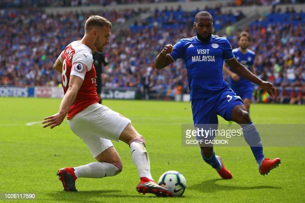 Arsenal's Welsh midfielder Aaron Ramsey vies with Cardiff City's Canadian midfielder Junior Hoilett during the English Premier League football match...