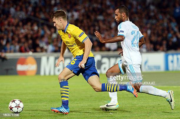 Arsenal's Welsh midfielder Aaron Ramsey vies with Marseille's Togolese midfielder JacquesAlaixys Romao before scoring a goal on September 18 2013 at...