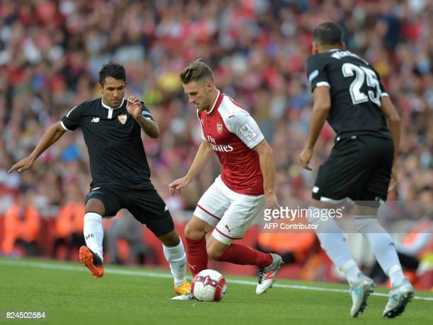 Arsenal's Welsh midfielder Aaron Ramsey vies with Sevilla's Gabriel Mercado during the preseason friendly football match between Arsenal and Sevilla...