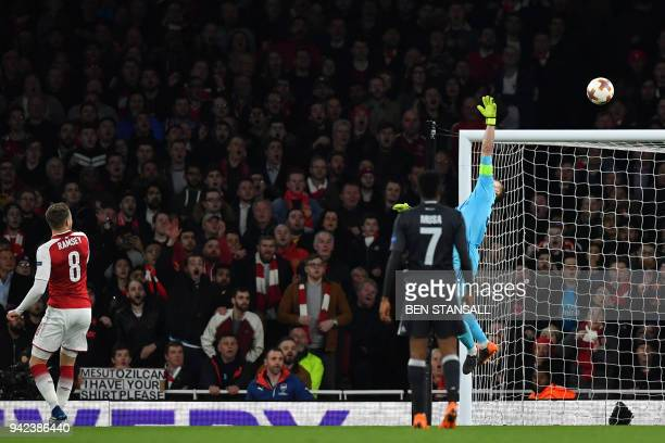 Arsenal's Welsh midfielder Aaron Ramsey watches his flick loop over CSKA Moscow's Russian goalkeeper Igor Akinfeev as he scores their third goal...