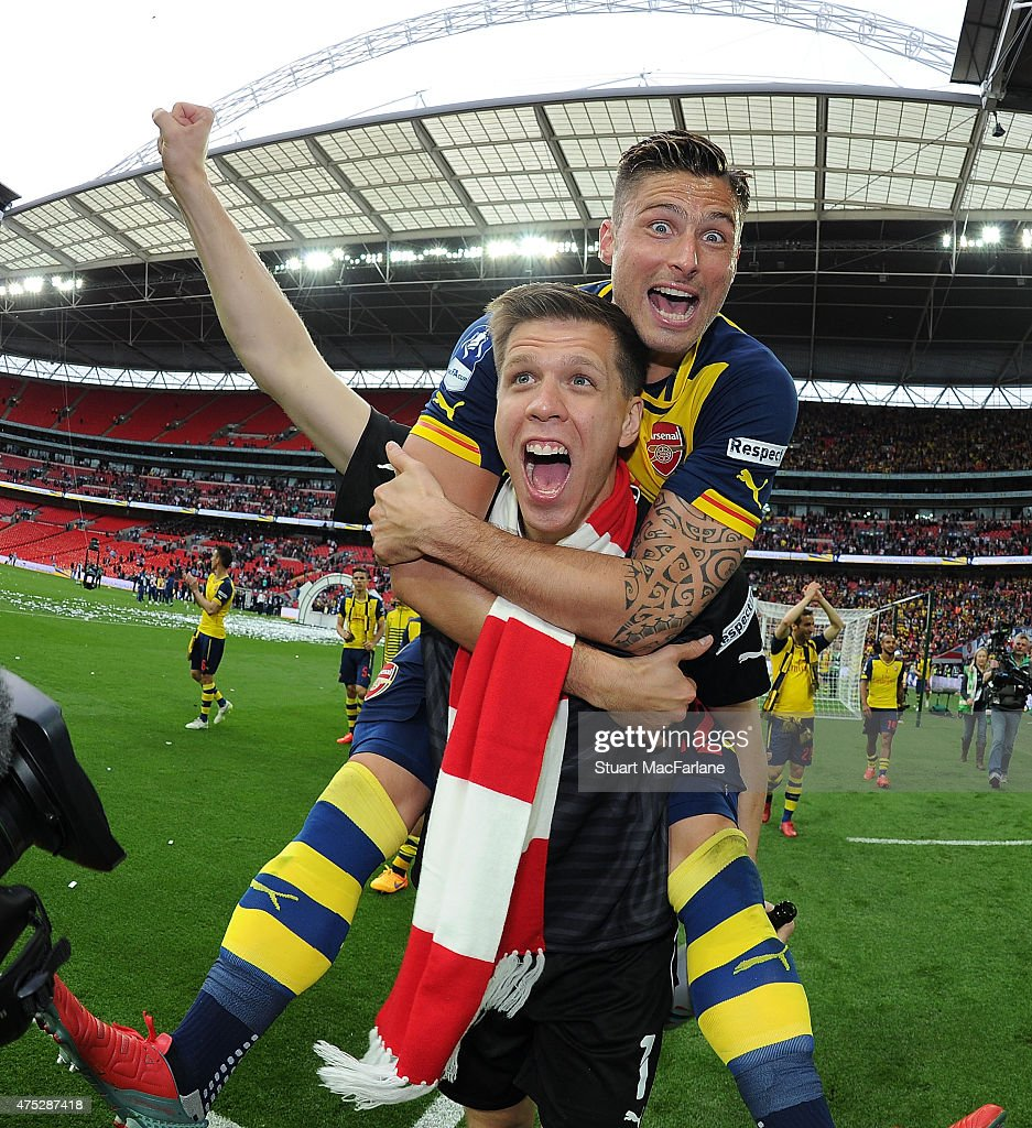 Arsenal's Wojciech Szczesny and Olivier Giroud celebrate after the FA Cup Final between Aston Villa and Arsenal at Wembley Stadium on May 30, 2015 in London, England.
