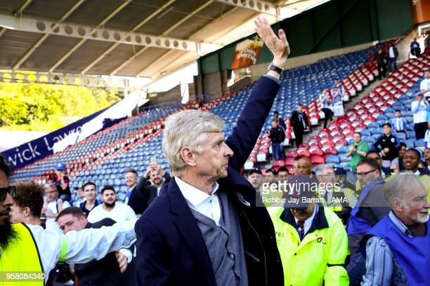 Arsene Wenger head coach / manager of Arsenal waves to the Arsenal fans at full time during the Premier League match between Huddersfield Town and...