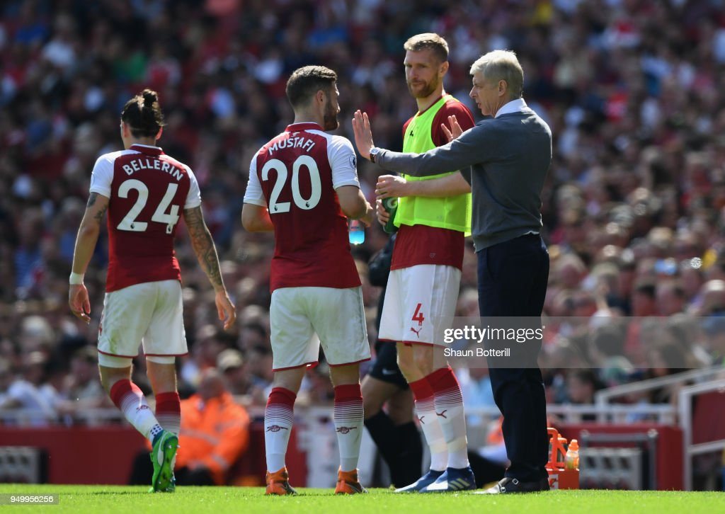 Arsene Wenger, Manager of Arsenal and Per Mertesacker talk to Shkodran Mustafi of Arsenal during the Premier League match between Arsenal and West Ham United at Emirates Stadium on April 22, 2018 in London, England.