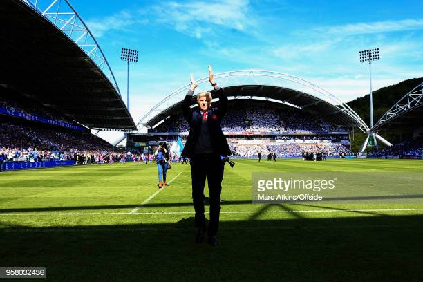 Arsene Wenger manager of Arsenal applauds in front of the fans before his final game in charge during the Premier League match between Huddersfield...