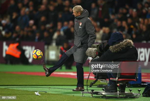 Arsene Wenger Manager of Arsenal controls the ball during the Premier League match between West Ham United and Arsenal at London Stadium on December...