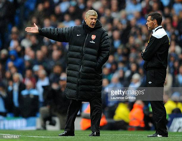 Arsene Wenger manager of Arsenal has words with fourth official Andre Marriner during the Barclays Premier League match between Manchester City and...