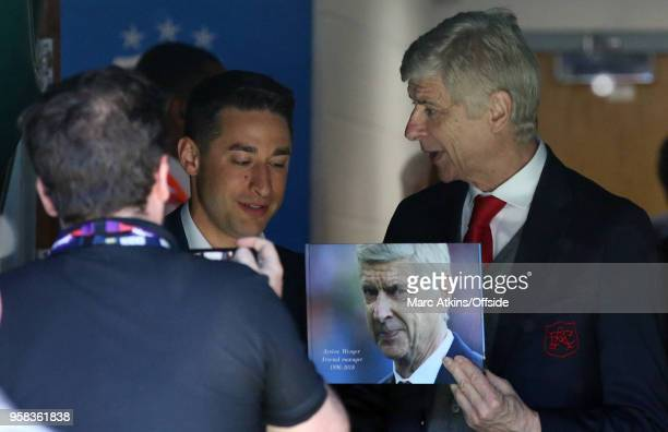 Arsene Wenger manager of Arsenal holds a photograph bearing the dates of his 22 years as manager during the Premier League match between Huddersfield...