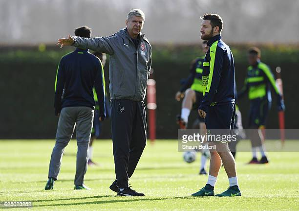 Arsene Wenger manager of Arsenal in discussion with Shkodran Mustafi during an Arsenal training session on the eve of their UEFA Champions League...