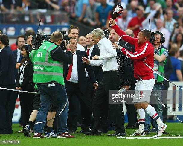 Arsene Wenger manager of Arsenal is showered with champagne by Lukas Podolski as they celebrate victory after the FA Cup with Budweiser Final match...