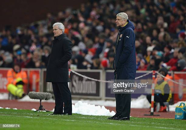 Arsene Wenger manager of Arsenal looks on with Mark Hughes manager of Stoke City during the Barclays Premier League match between Stoke City and...