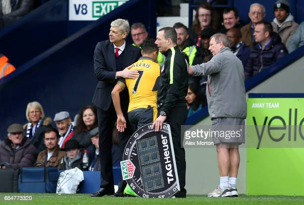 Arsene Wenger Manager of Arsenal pats Alexis Sanchez of Arsenal on the back after he is subbed during the Premier League match between West Bromwich...