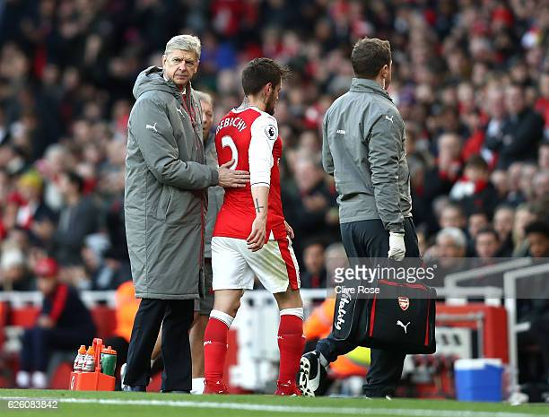 Arsene Wenger Manager of Arsenal pats Mathieu Debuchy of Arsenal on the back after he is forced off the pitch due to injury during the Premier League...