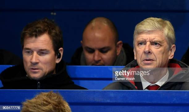 Arsene Wenger Manager of Arsenal sits in the stands with Jens Lehman during the Carabao Cup SemiFinal First Leg match between Chelsea and Arsenal at...