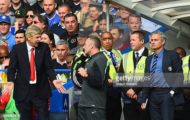 Arsene Wenger manager of Arsenal speaks to fourth official Jonathan Moss as Jose Mourinho manager of Chelsea looks on during the Barclays Premier...