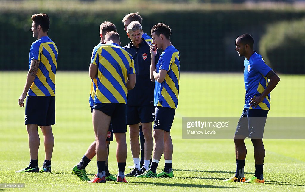 Arsene Wenger, manager of Arsenal talks to Laurent Koscielny during a training session ahead of their UEFA Champions League Play Off first leg match against Fenerbache at London Colney on August 20, 2013 in St Albans, England.