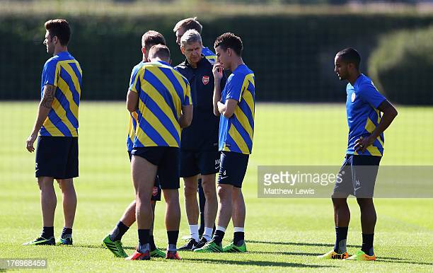 Arsene Wenger, manager of Arsenal talks to Laurent Koscielny during a training session ahead of their UEFA Champions League Play Off first leg match...