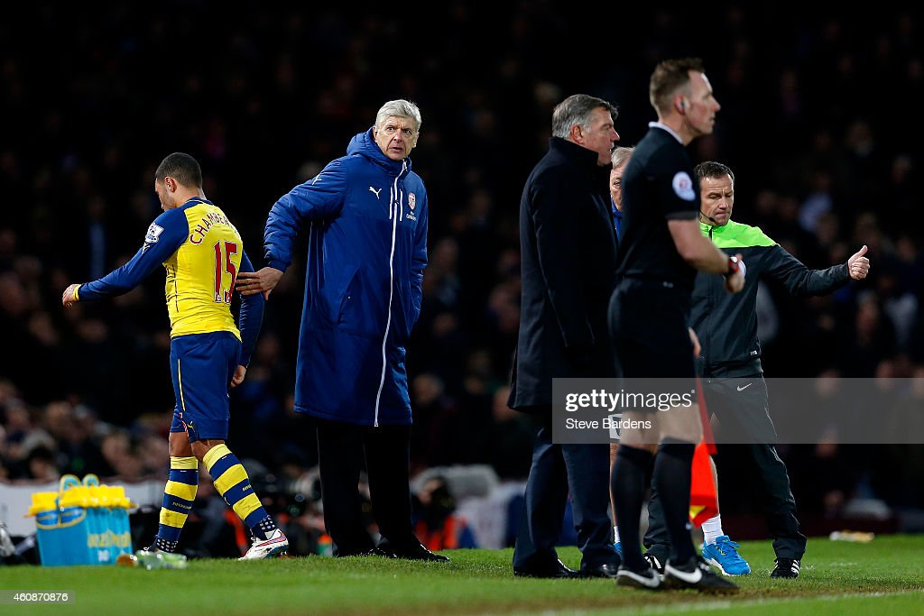 Arsene Wenger, manager of Arsenal taps Alex Oxlade-Chamberlain of Arsenal on the back as he is substituted during the Barclays Premier League match between West Ham United and Arsenal at Boleyn Ground on December 28, 2014 in London, England.