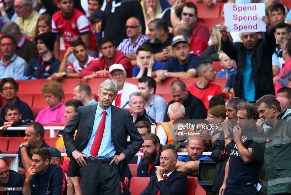 Arsene Wenger of Arsenal looks on as a fan behind makes his feelings known during the Barclays Premier League match between Arsenal and Aston Villa at Emirates Stadium on August 17, 2013 in London, England.