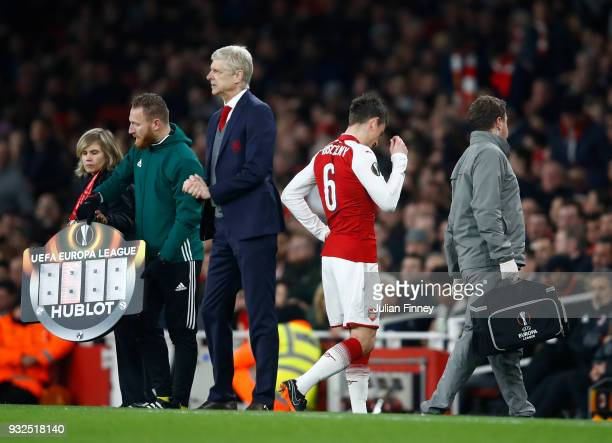 Arsene Wenger of Arsenal looks on as Laurent Koscielny leaves the pitch injured during the UEFA Europa League Round of 16 Second Leg match between...