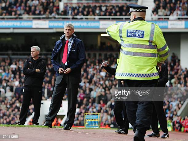 Arsene Wenger the Arsenal manager looks concerned after Robin Van Persie was apparently hit by an object thrown from the crowd during the Barclays...