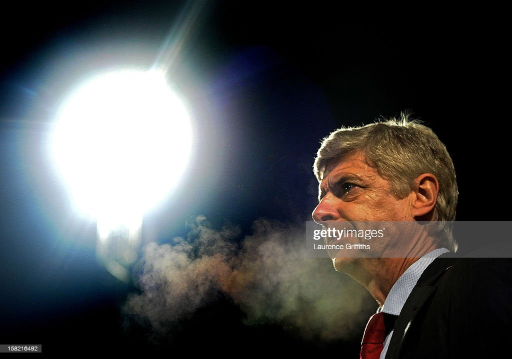 Arsene Wenger the Arsenal manager looks on during the Capital One Cup quarter final match between Bradford City and Arsenal at the Coral Windows Stadium, Valley Parade on December 11, 2012 in Bradford, England.