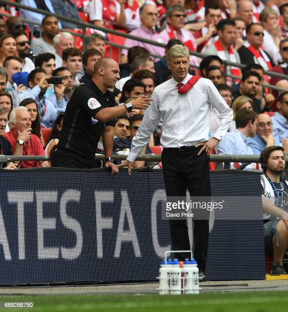 Arsene Wenger the Manager chats to 4th officla Bobby Madley during the match between Arsenal and Chelsea at Wembley Stadium on May 27 2017 in London...