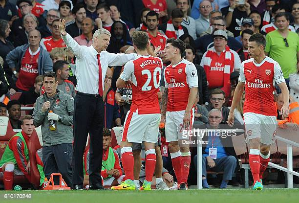 Arsene Wenger the Manager of Arsenal chats to Shkodran Mustafi and Hector Bellerin before the Premier League match between Arsenal and Chelsea at...