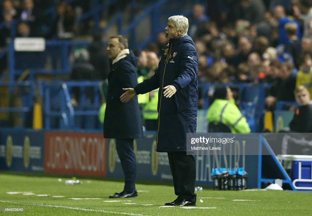 Arsene Wenger the manager of Arsenal gestures as Carlos Carvalhal the manager of Sheffield Wednesday looks on during the Capital One Cup fourth round match between Sheffield Wednesday and Arsenal at Hillsborough Stadium on October 27, 2015 in Sheffield, England.