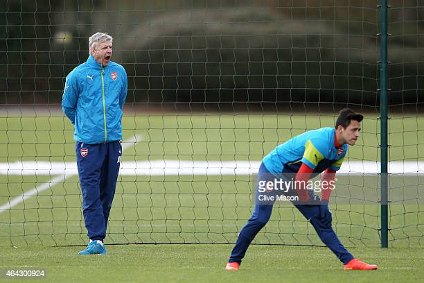 Arsene Wenger the manager of Arsenal looks on as Alexis Sanchez of Arsenal warms up during the Arsenal training session ahead of the UEFA Champions...