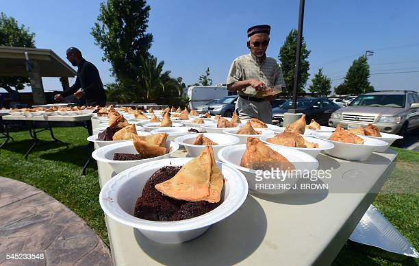 Arshad Farooq helps with preparing bowls of assorted snacks including Samosas and Chocolate cake for the feasting while celebrating Eid alFitr...