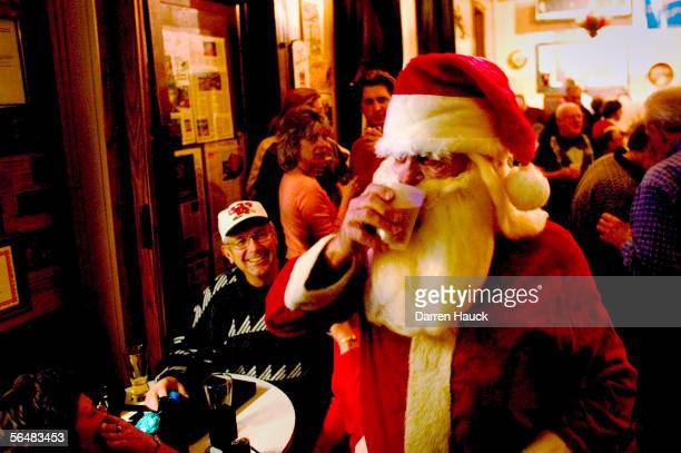 Art Altenburg Santa takes a drink of beer as he walks around celebrates at Art's Concertina bar annual Christmas party on December 22 2005 Milwaukee...