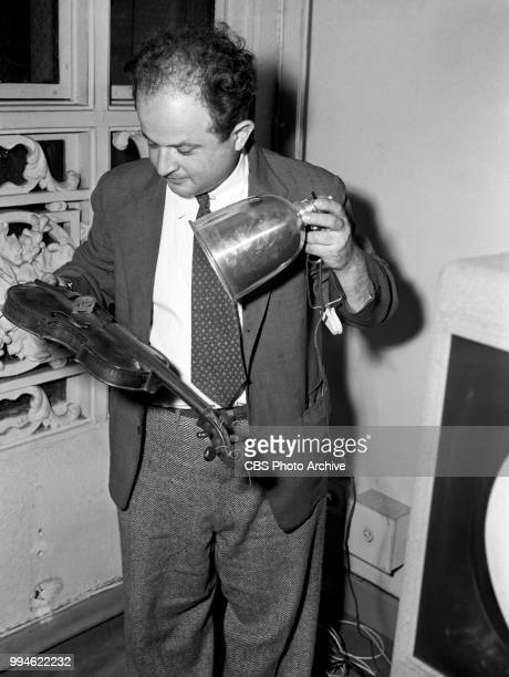 Art and antiques appraiser Sigmund Rothschild examines a violin on the CBS television program 'What's It Worth' Image dated June 8 1948 New York NY