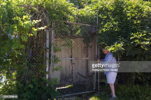 Art appraiser Bruce Gamage unlocks the padlock at the back entrance of Robert Indiana's home