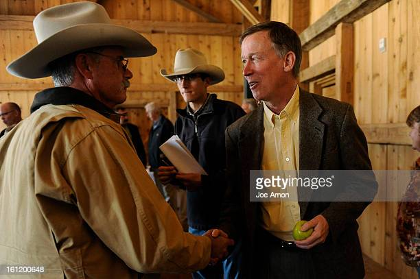 Art Bruchez owner of Reeder Creek Ranch shakes hands with Governor John Hickenlooper as his son Doug looks on after a press conference at Devil's...