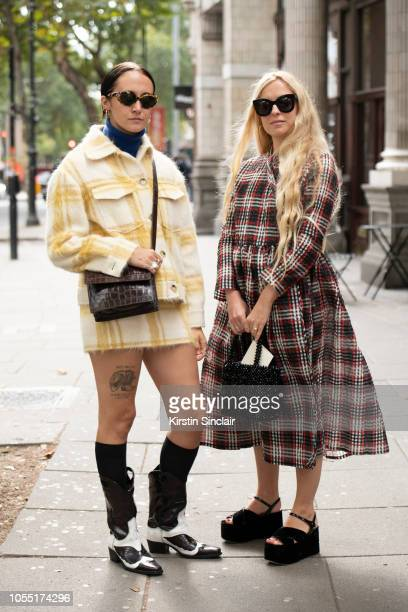 Art curator Antonia Marsh wears an Alexa Chung jacket skirt and boots with Founder of Shrimps Hannah Weiland wearing a Shrimps dress and bag during...