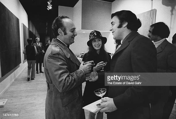 Art dealer and Director of OK Harris Gallery Ivan Karp his wife Marilyn Karp and artist Max Hutchinson at an opening party for a painting exhibition...