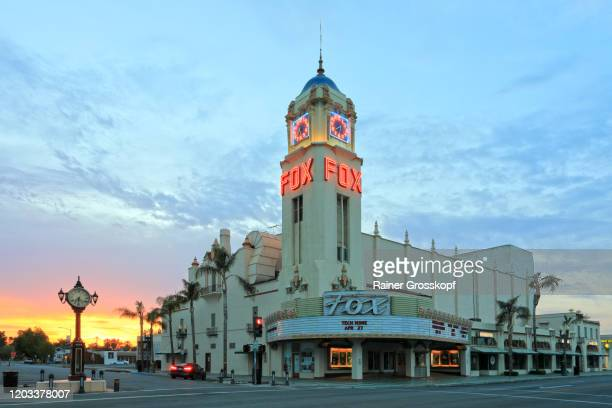 art deco building with tower illuminated at sunset - rainer grosskopf stock pictures, royalty-free photos & images