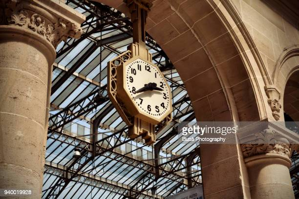 art deco clock hanging from arch at gare du nord station in paris, france - horloge photos et images de collection
