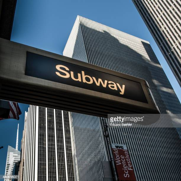 CONTENT] Art Deco fashioned Subway sign seen from very low perspective with skyscrapers and blue sky in the background