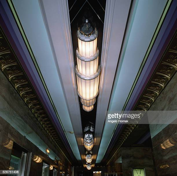 Art Deco light fittings by the bank of elevators in the entrance lobby of a building at 275 Madison Avenue. New York.