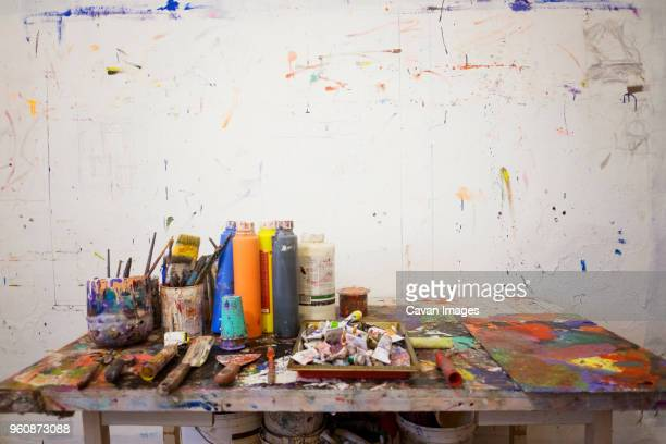 art equipment on messy table against wall - art studio stock pictures, royalty-free photos & images